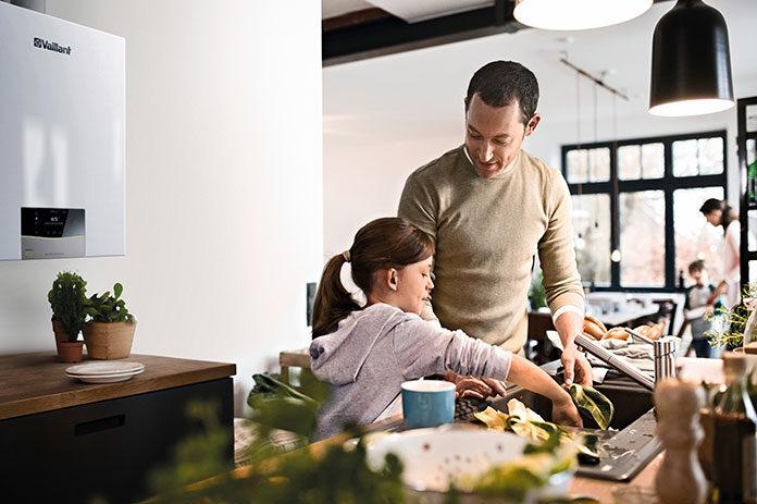 Mężczyzna gotuje z dzieckiem w kuchni, w której znajduje się gazowy kocioł kondensacyjny