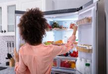 Kobieta stoi przed otwartą lodówką side by side i układa jedzenie na półkach